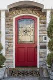 Puerta principal roja adornada de un hogar Foto de archivo libre de regalías