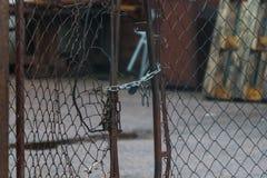 Puerta quebrada de la malla con una cerradura y una cadena imagenes de archivo