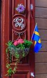Puerta roja adornada adornada con una bandera sueca y una maceta i Fotografía de archivo libre de regalías