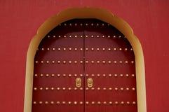 Puerta roja con la maneta de oro del león Fotos de archivo libres de regalías