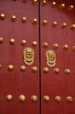 Puerta roja con la maneta de oro del león Fotografía de archivo