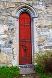 Puerta roja con los elementos de piedra tallados en el marco Foto de archivo libre de regalías