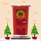 Puerta roja de la Navidad con la guirnalda, la nieve y el abeto imagenes de archivo