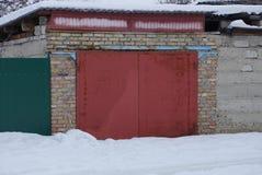 Puerta roja del hierro cerrado en una pared de ladrillo marrón de un garaje afuera en la nieve blanca imágenes de archivo libres de regalías