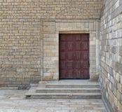Puerta roja grabada adornada de madera en las escaleras de la pared de piedra y de la cubierta de los ladrillos Imagenes de archivo