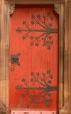 Puerta roja vieja con el ornamento de metal en una catedral i fotografía de archivo libre de regalías