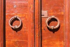 Puerta roja vieja con las manijas redondas del metal Orte, Italia imagen de archivo libre de regalías