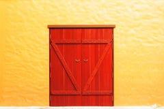Puerta roja vieja en pared amarilla Imagenes de archivo