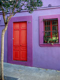 Puerta roja y pared púrpura Fotografía de archivo