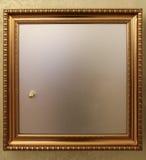 Puerta segura en la pared con un marco de oro Foto de archivo