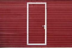 Puerta simple en pared roja Imagenes de archivo