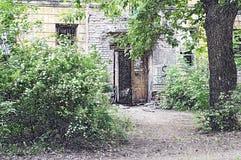 Puerta a una casa abandonada, colocándose en matorrales densos fotografía de archivo