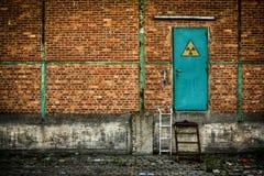 Puerta verde con la muestra nuclear en la pared de ladrillo Fotografía de archivo