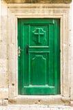 Puerta verde de madera vieja con la cruz cristiana en Kotor, Montenegro Imagenes de archivo