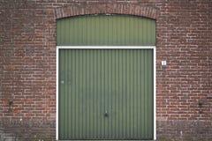Puerta verde del garaje con las paredes de ladrillo imagen de archivo