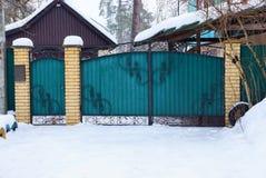 Puerta verde del metal cerrado con un modelo forjado negro en la calle en la nieve blanca fotos de archivo libres de regalías