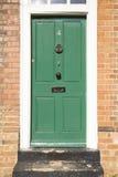 Puerta verde en un edificio de ladrillo Foto de archivo libre de regalías