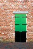 Puerta verde en una pared de ladrillo Imagen de archivo libre de regalías
