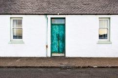 Puerta verde y dos ventanas en la casa blanca de la pared Fotografía de archivo libre de regalías