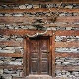 Puerta vieja de la casa, pared adornada con los cuernos Nakthan, valle de Parvati, Himachal Pradesh, la India imagenes de archivo