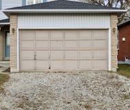 Puerta vieja del garage con una calzada de la grava Imagen de archivo