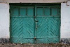 Puerta vieja del garaje en un muro de cemento blanco fotografía de archivo