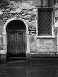 Puerta vieja en Venecia que se abre encendido en un canal Imagen de archivo libre de regalías