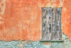 Puerta vieja por una pared anaranjada Imagenes de archivo