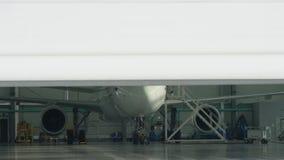 Puerta y avión del obturador del rodillo en fondo del hangar El aeroplano del jet del negocio está en hangar Jet corporativo priv almacen de metraje de vídeo