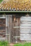 Puerta y azotea de granero cubiertas con el musgo imagen de archivo