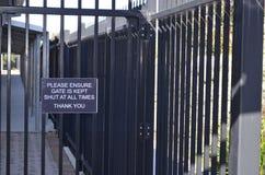 Puerta y cerca negras con la muestra Imagen de archivo