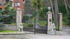 Puerta y estatuas calzadas de leones en una entrada en el territorio de la cabaña Foto de archivo libre de regalías