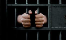 Puerta y manos de la celda de prisión Imagen de archivo