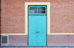Puerta y pared de ladrillo de madera azules fotografía de archivo