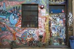 Puerta y pared marcadas con etiqueta con la pintada en Williamsburg Brooklyn Imágenes de archivo libres de regalías