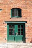 Puerta y ventana verdes en pared de ladrillo Foto de archivo