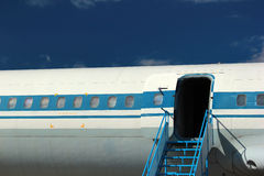Puerta y ventanas viejas de aviones de pasajero contra fondo del cielo azul Imagen de archivo