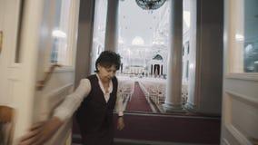 Puertas abiertas de la mujer mayor móvil del tiro adentro al pasillo brillante vacío del órgano con la porción de asientos metrajes