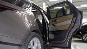 Puertas abiertas del nuevo coche en salón del coche acci?n Vista del interior del nuevo coche costoso con la puerta abierta Marca almacen de video