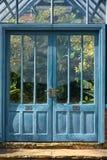 Puertas antiguas azules al invernadero tropical fotos de archivo