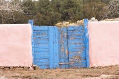 Puertas azules resistidas con las paredes rosadas del adobe foto de archivo