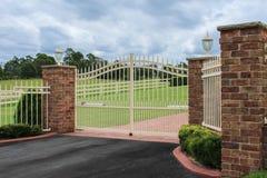 Puertas blancas de la entrada de la calzada del hierro labrado Foto de archivo libre de regalías