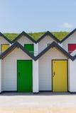 Puertas coloridas de amarillo y de verde, con cada uno que es numerado individualmente, de las casas de playa blancas en un día s Imágenes de archivo libres de regalías