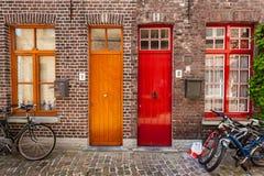 Puertas de casas y de bicicletas viejas en la ciudad europea Brujas (Brujas foto de archivo