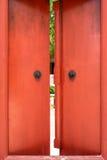 Puertas de madera rojas viejas con la manija del anillo del metal Foto de archivo libre de regalías