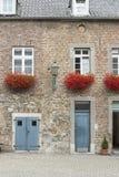 Puertas del edificio y flores rojas en Aquisgrán Imagenes de archivo