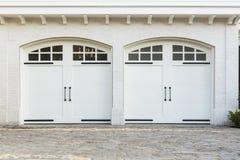 Puertas dobles gemelas del garaje a un hogar blanco Imagen de archivo
