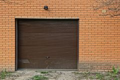 Puertas marrones cerradas en la pared de ladrillo del garaje imagen de archivo libre de regalías