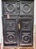 puertas negras de madera antiguas con lleno y el tirador de puerta foto de archivo