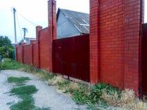 Puertas oxidadas de acero y una cerca del ladrillo rojo Fotos de archivo
